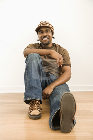 Handsome mid adult man. stock photo, African-American mid-adult man wearing hat sitting on floor smiling at viewer. by Iofoto Images