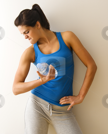 Strong female stock photo, Portrait of woman in fitness attire flexing arm muscle holding water bottle. by Iofoto Images