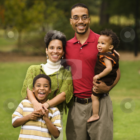 Family of four stock photo, Portrait of happy smiling family of four in park. by Iofoto Images