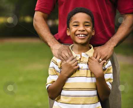 Father and son stock photo, Father standing behind son with hands on his shoulders as boy smiles. by Iofoto Images
