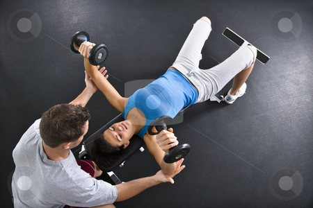 Woman lifting weights stock photo, Man assisting woman lifting weights at gym. by Iofoto Images