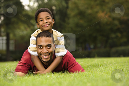 Father and son stock photo, Father lying in grass smiling as son climbs on his back and hugs his neck. by Iofoto Images