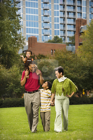 Family in park stock photo, Family of four people walking in park smiling. by Iofoto Images