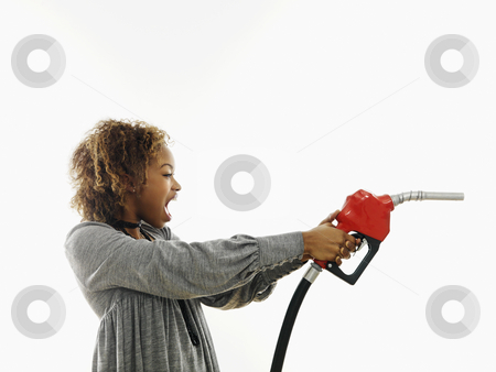 Angry woman with gas nozzle stock photo, Portrait of pretty young woman holding gas pump nozzle like a gun making angry facial expression on white background. by Iofoto Images