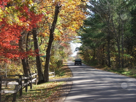 Blazing Fall Colors stock photo, This picturesque view of blazing fall colors on a back road near Cross Lake, MN  suggests a relaxing escape (October, 2007). by Dennis Thomsen