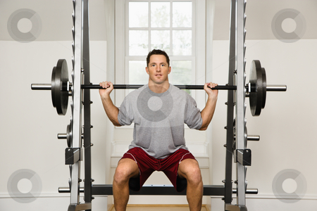 Man lifting weights stock photo, Man lifting weights in gym. by Iofoto Images