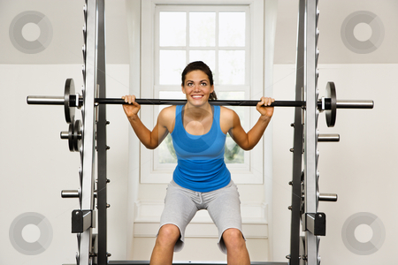 Fitness woman stock photo, Woman lifting weights in gym smiling. by Iofoto Images