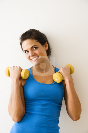Woman strength training stock photo, Woman holding hand weights and smiling. by Iofoto Images