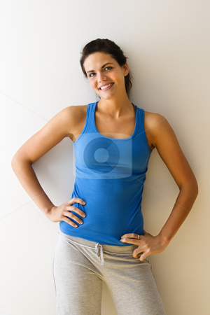 Woman in workout clothes stock photo, Portrait of woman in fitness attire smiling with hands on hips. by Iofoto Images