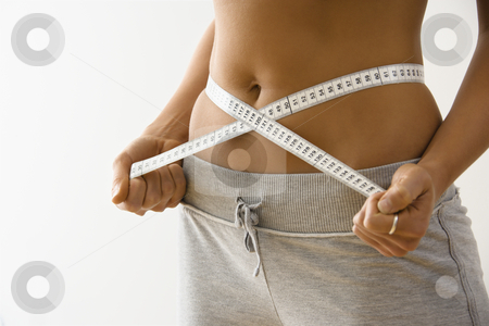 Woman losing weight stock photo, Woman standing pulling measuring tape around waist. by Iofoto Images