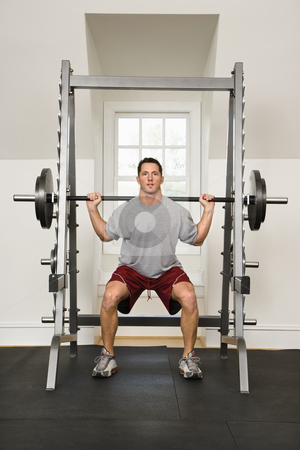 Fitness training stock photo, Man lifting weights in gym. by Iofoto Images