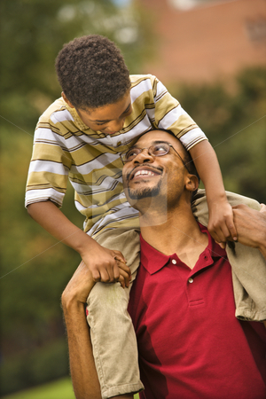 Father carrying son stock photo, Father carrying his son on his shoulders smiling and looking at eachother. by Iofoto Images