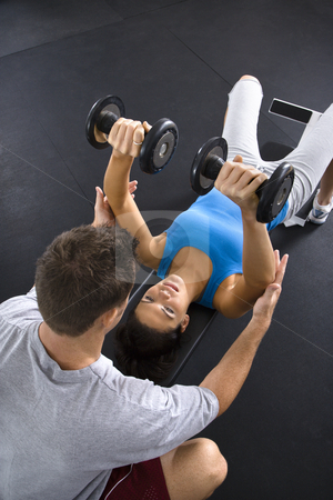 Fitness training stock photo, Man assisting woman lifting weights at gym. by Iofoto Images