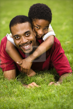 Father and son playing stock photo, Father lying in grass smiling as son climbs on his back and hugs his neck. by Iofoto Images
