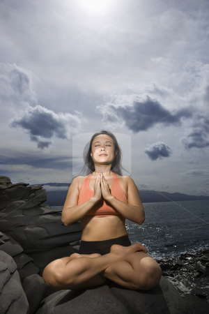 Woman meditating stock photo, Asian woman sitting on rock by ocean in lotus pose with eyes closed in Maui, Hawaii by Iofoto Images