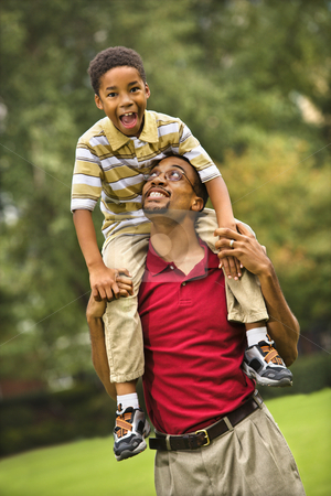 Father and son bonding stock photo, Father carrying his son on his shoulders smiling and looking at eachother. by Iofoto Images