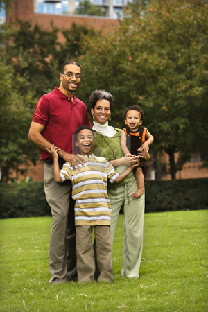 Family portrait stock photo, Family of four standing in park smiing. by Iofoto Images