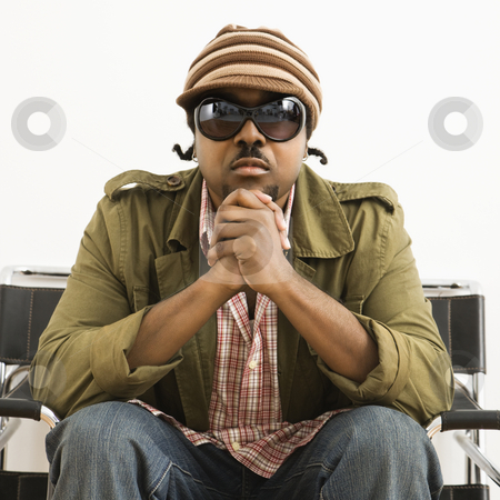 Serious stylish man. stock photo, African-American mid-adult man wearing hat and sunglasses and looking at viewer. by Iofoto Images