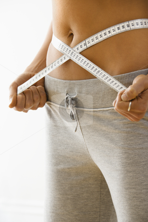 Woman on diet stock photo, Woman standing pulling measuring tape around waist. by Iofoto Images