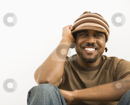 Handsome man smiling. stock photo, African-American mid-adult man wearing knit hat smiling at viewer. by Iofoto Images