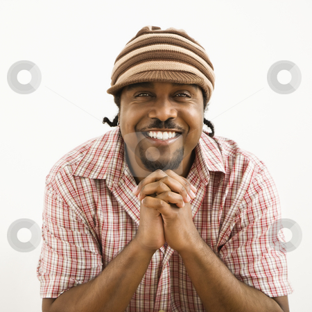 Handsome man smiling. stock photo, African-American mid-adult man wearing hat and smiling at viewer with hands together. by Iofoto Images