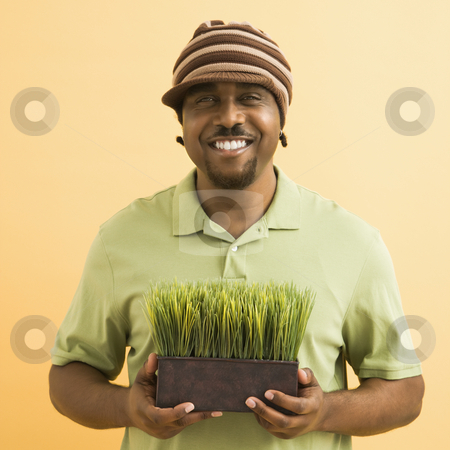 Man holding plant. stock photo, African-American mid-adult man wearing hat holding potted grass smiling at viewer. by Iofoto Images