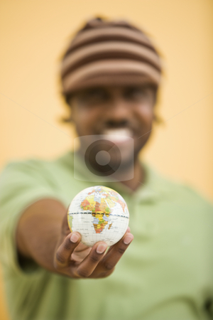 Man with small globe. stock photo, African-American mid-adult man wearing hat holding small globe to viewer. by Iofoto Images
