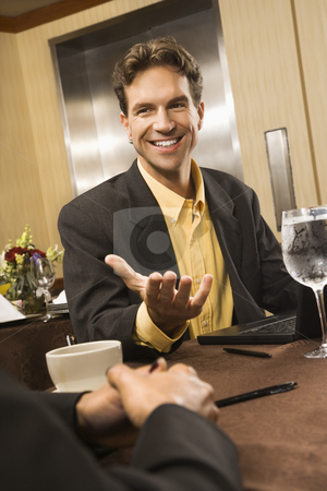 Businessman in conversation. stock photo, Caucasian businessman gesturing during meeting. by Iofoto Images