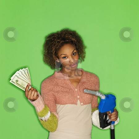 Fuel cost concept stock photo, Portrait of pretty young woman standing against green background holding gasoline pump nozzle and money. by Iofoto Images