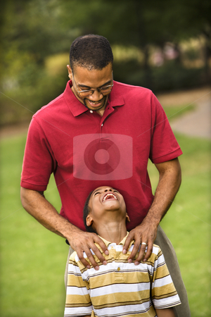 Dad and son stock photo, Father standing behind son with hands on his shoulders as boy smiles. by Iofoto Images