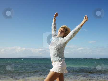 Joyful woman in Maui stock photo, Portrait of attractive young blond woman smiling with arms raised in air on Maui, Hawaii beach. by Iofoto Images
