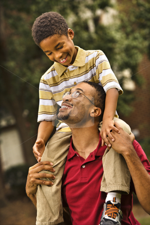 Dad carrying son stock photo, Father carrying his son on his shoulders smiling and looking at eachother. by Iofoto Images