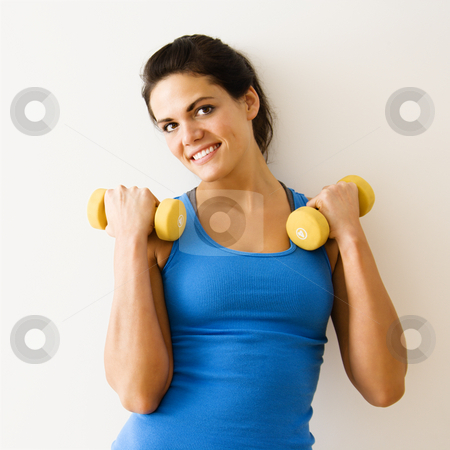Woman doing workout stock photo, Woman holding hand weights and smiling. by Iofoto Images