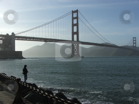 Silhouette of Fisherman and Golden Gate Bridge stock photo, A lone fisherman tries his luck with San Francisco's Golden Gate Bridge silouetted by the late afternoon sun in the background. by Dennis Thomsen