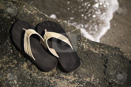 Sandals by the shore stock photo, Sandals on a rock with ocean wave in the background by Scott Griessel