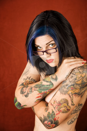 Woman with tattoos and crossed arms stock photo, Pretty young woman with many tattoos crossing her arms by Scott Griessel