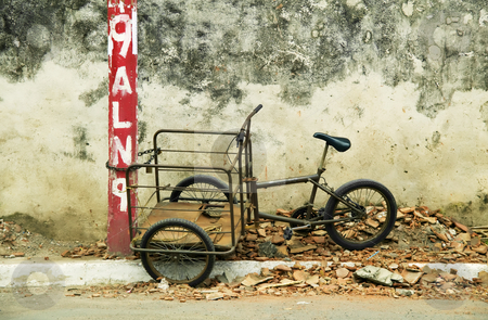 Tricycle chained to a post in Nicaragua stock photo, Tricycle chained to a red post roadside in Granada Nicaragua by Scott Griessel