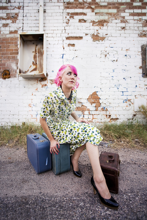 Woman with Pink Hair and a Small Suitcases stock photo, Woman with pink hair wearing polka dot dress in alley with suitcases by Scott Griessel