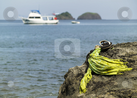 Sandals by the shore stock photo, Sandals on a rock with ocean and boat in the background by Scott Griessel
