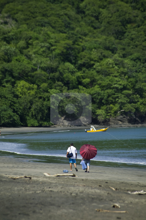 Walking on the Beach in Costa Rica stock photo, Man and woman walking on the beach with jungle in the background by Scott Griessel