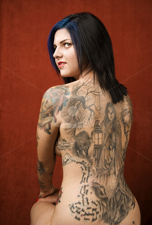 Woman with a tattoo on her back stock photo, Woman with many tattoos on her back and arms by Scott Griessel