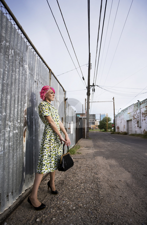 Woman with Pink Hair and a Purse in an Alley stock photo, Woman with pink hair wearing polka dot dress in alley with purse by Scott Griessel