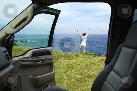 Happy woman near ocean. stock photo, Excited woman standing on grassy cliff by Pacific Ocean in Maui, Hawaii. by Iofoto Images