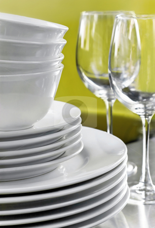 Stack of Commercial White Plates Bowls & Wine Glasses stock photo, Generic stack of dishes with green background by Mark S