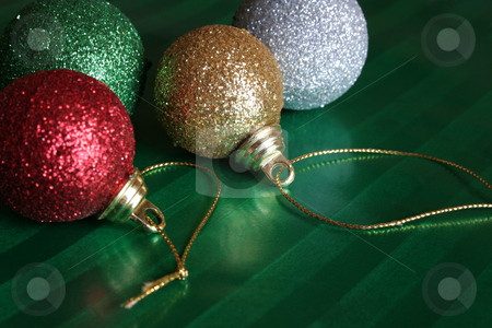 Four Shiny Christmas Balls stock photo, Four shiny christmas balls resting on green wrapping paper. by Chris Hill