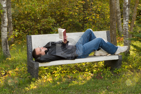 Reading stock photo, A man lying on a bench reading a book by Richard Nelson