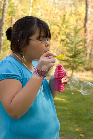 Girl Blowing Bubbles stock photo, Nine year old girl blowing bubbles outside by Richard Nelson