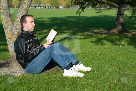 Man Reading Outside stock photo, A young man reading a novel outside by Richard Nelson