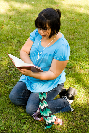 Story Time stock photo, Nine year old girl sitting in the grass reading by Richard Nelson