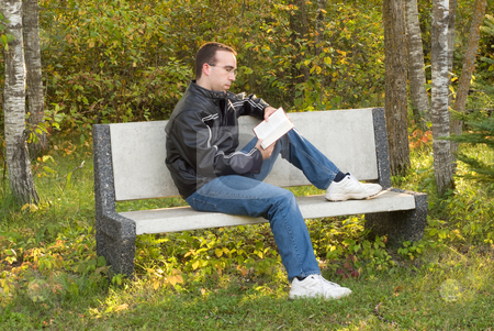 Man Reading on a Bench stock photo, A young caucasian man sitting on a park bench reading outside by Richard Nelson